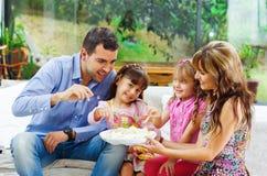 有吃从a的两个女儿的西班牙父母 免版税库存图片