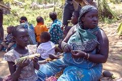 有吃Hadzabe部落的甘蔗的婴孩的画象妇女 免版税库存图片