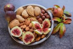有各种各样的坚果和无花果的板材 石榴小树枝  STI 免版税库存图片