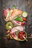 有各种各样的开胃小菜、ciabatta面包、pesto和火腿的意大利肉板材在土气木背景,顶视图 库存照片