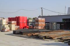 有各种各样的材料的建造场所建筑的 金属管子和渠道,栅格 具体建筑和砖 免版税图库摄影