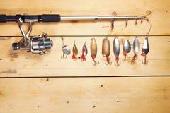 有各种各样的金属诱饵的钓鱼竿在木板 免版税库存图片