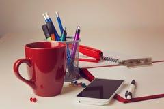 有各种各样的项目的办公桌包括咖啡杯和巧妙的电话在迷离背景 免版税库存图片