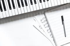 有合成器的笔记本在dj或音乐家工作白色书桌背景顶视图大模型的音乐演播室 库存照片