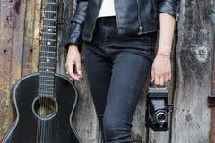 有吉他和一台老照相机的女孩 库存照片