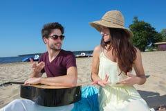 有吉他和女朋友的年轻人海滩的 免版税库存照片