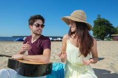 有吉他和女朋友的年轻人海滩的 库存照片