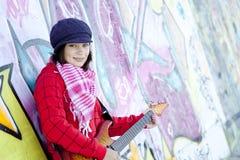 有吉他和街道画的女孩 图库摄影