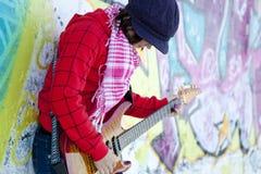 有吉他和街道画的女孩 免版税库存图片