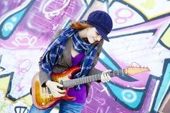 有吉他和街道画的女孩 免版税库存照片