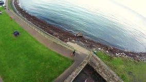 有吉他的人走在海旁边的 免版税图库摄影