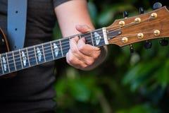 有吉他的吉他演奏员在手中 免版税库存图片