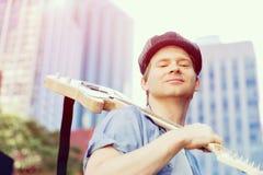 有吉他的年轻音乐家在城市 免版税库存图片
