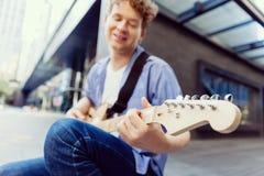 有吉他的年轻音乐家在城市 免版税库存照片
