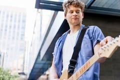 有吉他的年轻音乐家在城市 免版税图库摄影