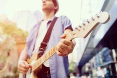 有吉他的年轻音乐家在城市 库存照片