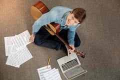 有吉他的微笑对照相机的年轻人顶视图  免版税库存图片
