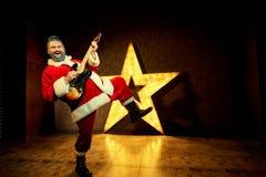 有吉他的愉快的圣诞老人跳舞以a为背景 库存图片