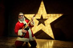 有吉他的愉快的圣诞老人跳舞以a为背景 免版税库存照片