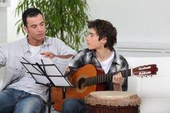 有吉他的父亲和儿子 库存照片