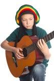 有吉他和帽子的欧洲男孩有dreadlocks的 免版税库存照片