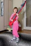 有吉他和溜冰鞋的滑稽的孩子 免版税库存照片