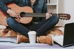 有吉他和电话的人 库存图片