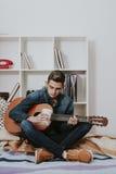 有吉他和电话的人 免版税库存图片
