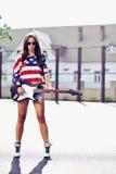 有吉他室外时尚画象的年轻时髦的妇女 免版税库存图片
