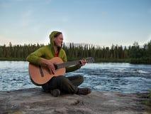 有吉他的一个微笑的女孩坐岩石 免版税库存图片