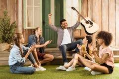 有吉他的不同种族的朋友一起花费时间的 库存图片