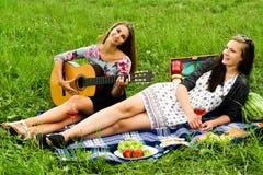 有吉他的两个女孩在野餐期间 免版税库存图片