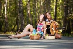 有吉他的两个嬉皮女孩在夏天森林里 免版税库存照片