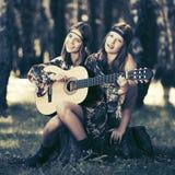 有吉他的两个时尚女孩在夏天森林里 库存照片