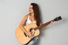 有吉他的华美的女孩在手上 免版税库存图片