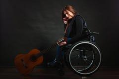 有吉他的哀伤的残疾女孩 免版税库存图片