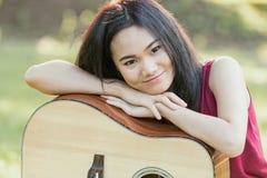 有吉他的女孩在庭院里 免版税库存图片
