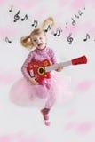有吉他的女孩在音乐注意背景 免版税库存照片