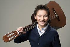 有吉他的微笑的男孩 免版税库存图片