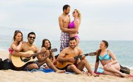 有吉他的朋友在海滩 免版税库存图片