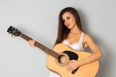 有吉他的秀丽年轻深色的妇女 免版税库存图片