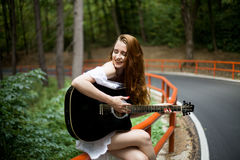 有吉他的红头发人女孩唱歌在旅行的 免版税库存照片