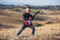有吉他的逗人喜爱的男孩 图库摄影