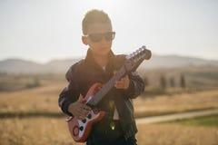 有吉他的逗人喜爱的男孩 库存图片