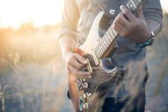 有吉他的音乐家在日落领域,音乐背景,葡萄酒 免版税库存照片