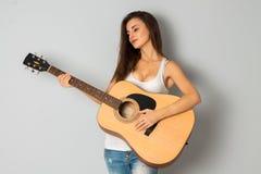 有吉他的年轻深色的妇女 库存照片