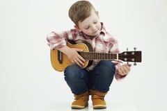 有吉他的滑稽的儿童男孩 演奏音乐的乡村男孩 库存图片