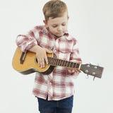有吉他的滑稽的儿童男孩 演奏音乐的乡村男孩 图库摄影