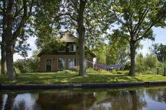 有吊床的田园诗房子在树之间 免版税库存图片
