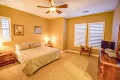 有吊扇和快门的温暖的卧室 免版税库存图片